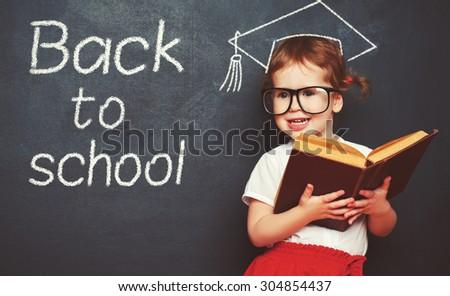 pretty little girl schoolgirl with books  in a school board - stock photo