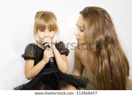 Pretty little girl singing in microphone, mother and little girl with a microphone - stock photo