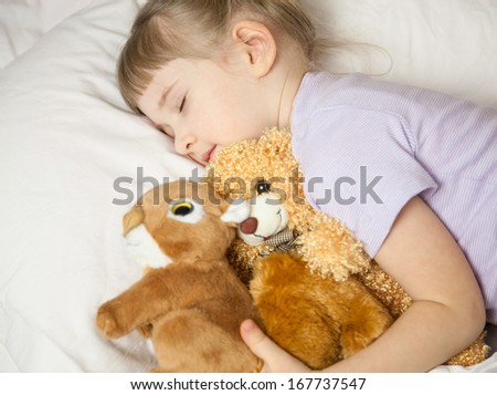 Pretty little girl sleeping in a bed - stock photo