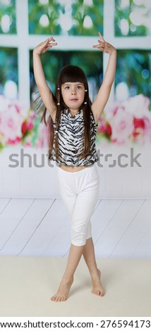 Pretty little girl stands with her hands up ready to dance - stock photo