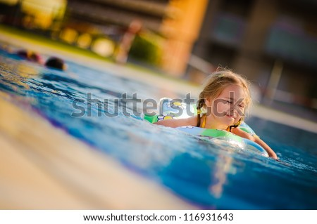 Pretty little girl swimming in outdoor pool and have a fun with inflatable circle - stock photo