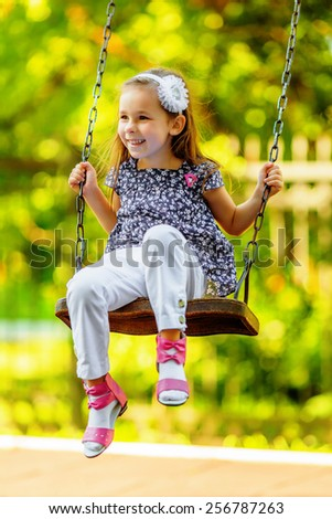 Pretty little girl swinging on seesaw in summertime - stock photo