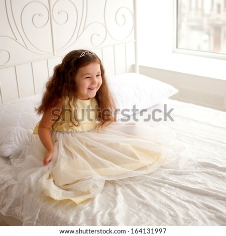 Pretty little girl waking up in the morning. Dream the little princess on a white bed. - stock photo