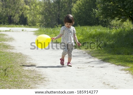 Pretty little girl walks in the park - stock photo