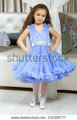 Pretty little girl wearing lace blue dress posing indoors - stock photo