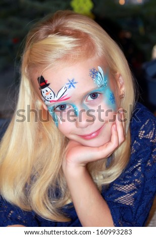 Pretty little girl with a painted face. Christmas face painting. - stock photo