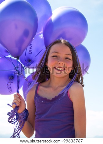 Pretty little girl with baloons in hand - stock photo