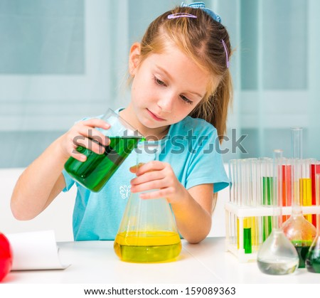 pretty little girl with flasks for chemistry - stock photo