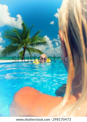 Pretty little girl with her mother in swimming pool outdoors - stock photo