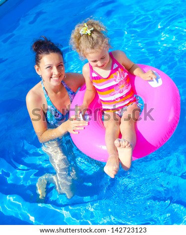 Pretty little girl with her mother in swimming pool outdoors. Vertical view - stock photo
