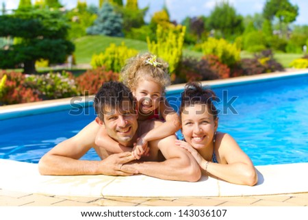 Pretty little girl with her parent in swimming pool outdoors - stock photo