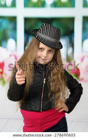 Pretty little girl with long hair dressed in black and red clothes and hat shows thumbs up - children beauty and fashion concept - stock photo