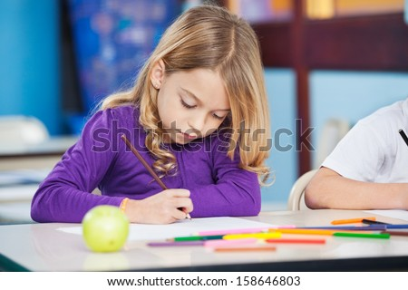 Pretty little girl with sketch pen drawing in kindergarten - stock photo