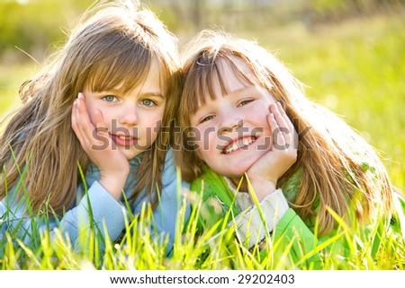 Pretty little girls on green summer grass - stock photo