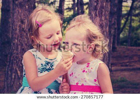 Pretty little girls (sisters) eating ice cream in the summer the Park. The image is tinted. - stock photo