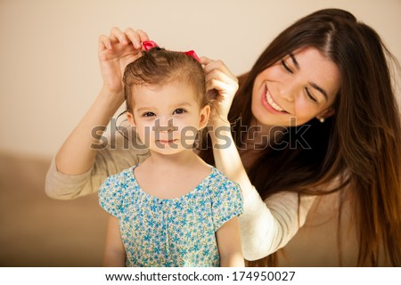 Pretty little Hispanic girl getting her hair done by her mom before they go out together - stock photo