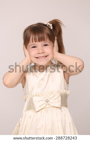 Pretty little mummy's lady closed her ears. Girl in white dress with ponytail smiling. - stock photo