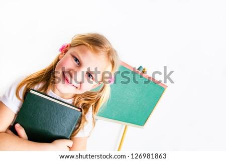 Pretty little schoolgirl posing  in front of the blackboard - stock photo