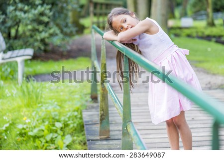 pretty little thai girl leaning on a bridge - stock photo