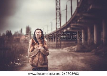 Pretty long hair brunette girl with old industrial bridge behind, grain effect - stock photo