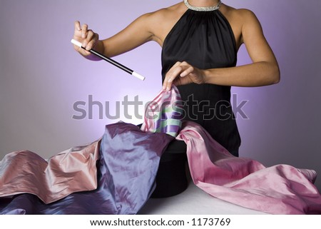 Pretty magician pulling fabric out of a hat - stock photo