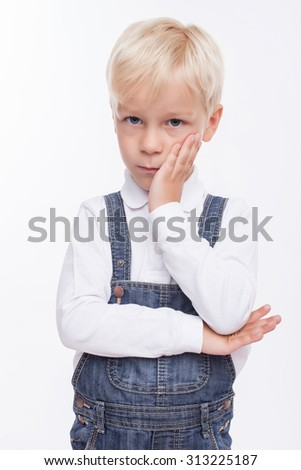 Pretty male child is bored. He is looking at the camera with sadness. The schoolboy is standing and touching his cheek. Isolated on background - stock photo