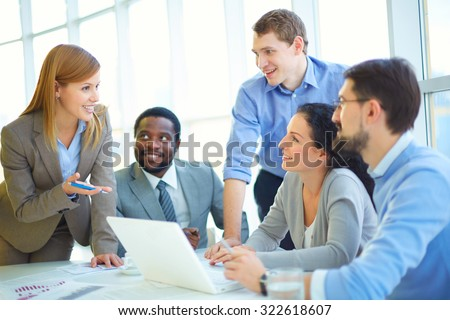 Pretty manager explaining her viewpoint upon project to co-workers - stock photo