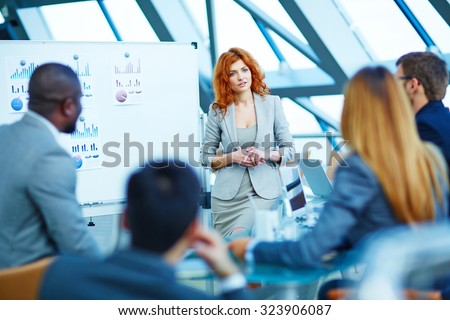 Pretty manager listening to colleagues after explanation of her idea - stock photo