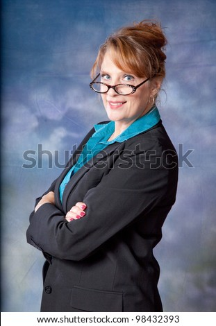 Pretty, mature businesswoman with a happy expression, looking at the camera with her arms crossed across her chest and a smile - stock photo