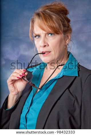Pretty, mature businesswoman with a thoughtful expression, looking at the camera and holding some eye glasses in her hand - stock photo