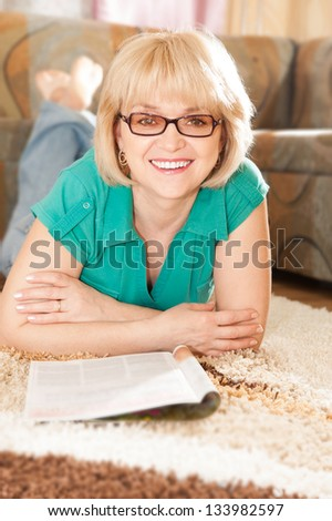 Pretty mature lady lying on carpet smiling  and reading magazine - stock photo