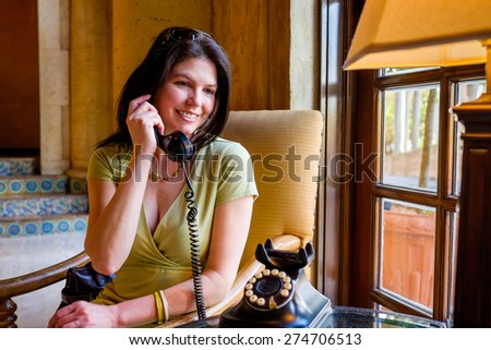 Pretty middle age woman indoor portrait using a vintage telephone. - stock photo