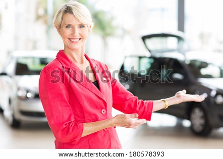 pretty middle aged saleswoman doing welcoming gesture in showroom - stock photo