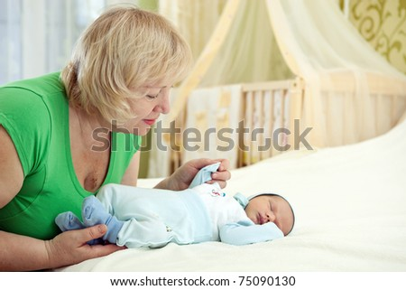 Pretty middle-aged woman holding her newborn grandson - stock photo