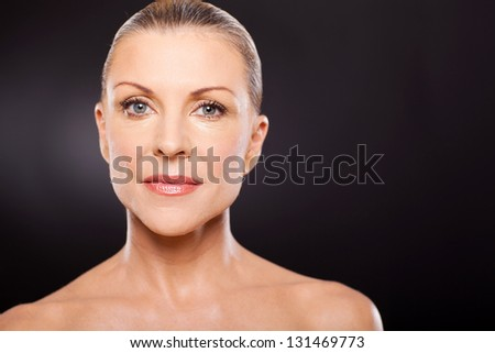 pretty middle aged woman on black background - stock photo