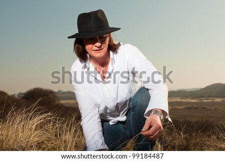 Pretty middle aged woman with hat enjoying outdoors. Feeling free in grassy dunes landscape. Clear sunny spring day with blue sky. - stock photo