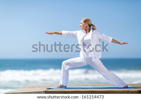 pretty middle aged woman yoga pose by the beach - stock photo