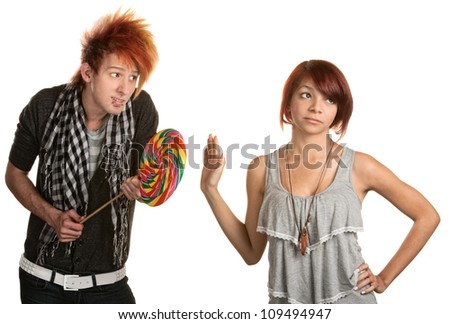 Pretty mixed race girl dismisses naive man with lollipop - stock photo