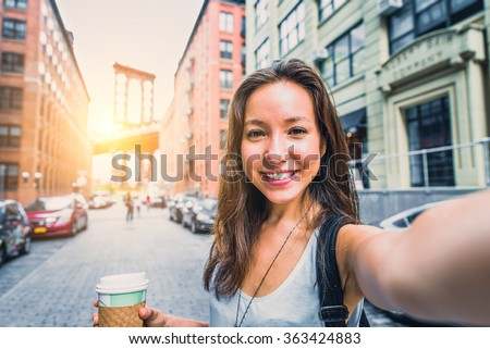 Pretty mixed race woman taking a selfie in New York, Brooklyn Bridge in the background - Beautiful girl walking on the streets of NY and photographing some landmarks - stock photo