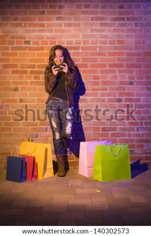 Pretty Mixed Race Young Adult Woman with Shopping Bags Using Her Cell Phone Against a Brick Wall - Plenty of Copy Space. - stock photo