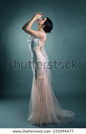 Pretty model posing in wedding dress with crystals - stock photo