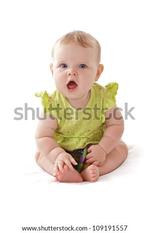 Pretty 6 month old baby girl with big blue eyes and ruffled dress sits and vocalizes. She holds a rattle. Pastels, isolated on white background, vertical, copy space. - stock photo