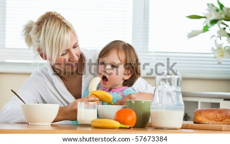 Pretty mother and daughter having breakfast in the kitchen - stock photo