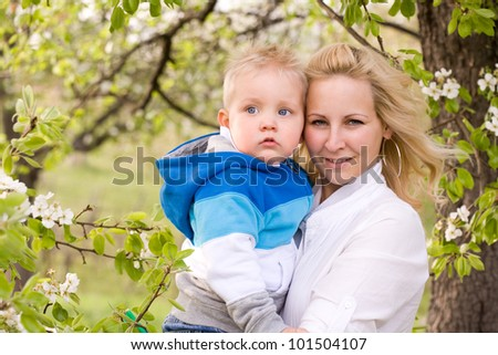 Pretty mother and her baby son outdoors in blooming spring nature. - stock photo
