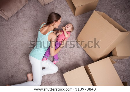 Pretty mother and her little child are lying on flooring near cardboard boxes. They are preparing to move in a new house. The woman is tickling her daughter with joy. They are laughing - stock photo