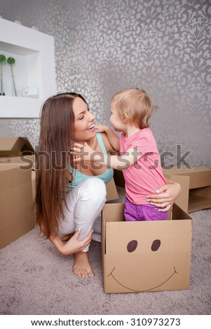 Pretty mother and little daughter are preparing to move in new apartment. The child is standing in the box with joy. The woman is embracing the girl and smiling - stock photo