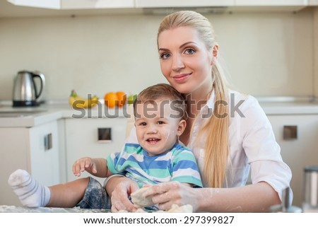 Pretty mother is sitting at the table and holding her little son on her knees. They are doing dough for pastry. The family is smiling with enjoyment - stock photo