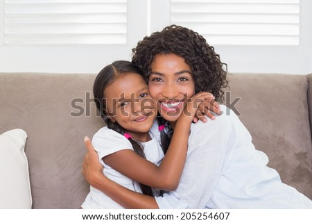 Pretty mother sitting on the couch with her daughter smiling at camera at home in the living room - stock photo