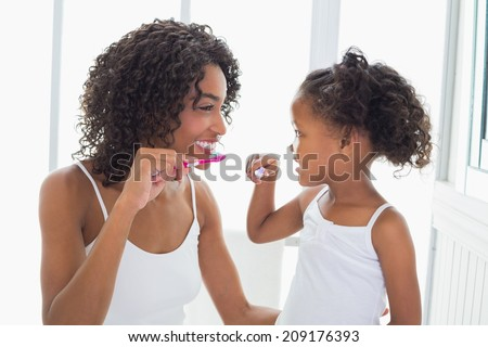 Pretty mother with her daughter brushing their teeth at home in the bathroom - stock photo