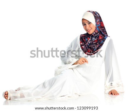 Pretty muslim woman model in action sitting on the floor, on white background - stock photo